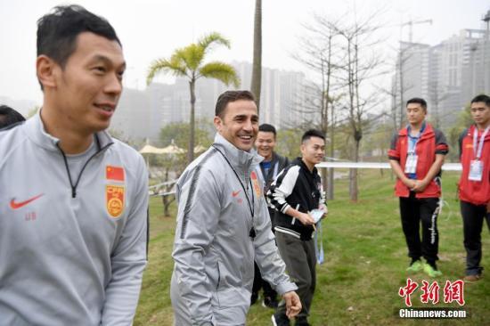 资料图:卡纳瓦罗前往训练场时,与团队成员开着玩笑。 俞靖 摄