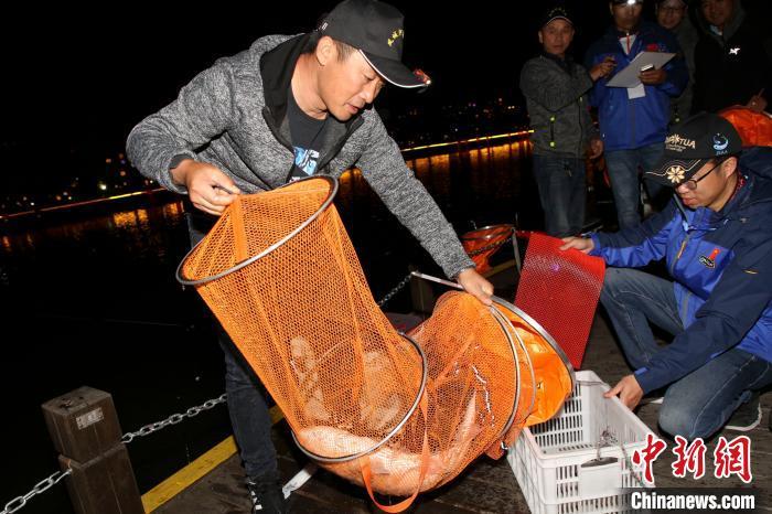 工作人员正在清点参赛选手的鱼篓。 汤德宏 摄